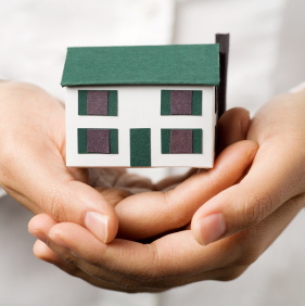 A pair of hands holding a small house.  Real estate or insurance concept.